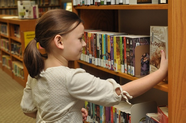 Girl looking at books on library bookshelf